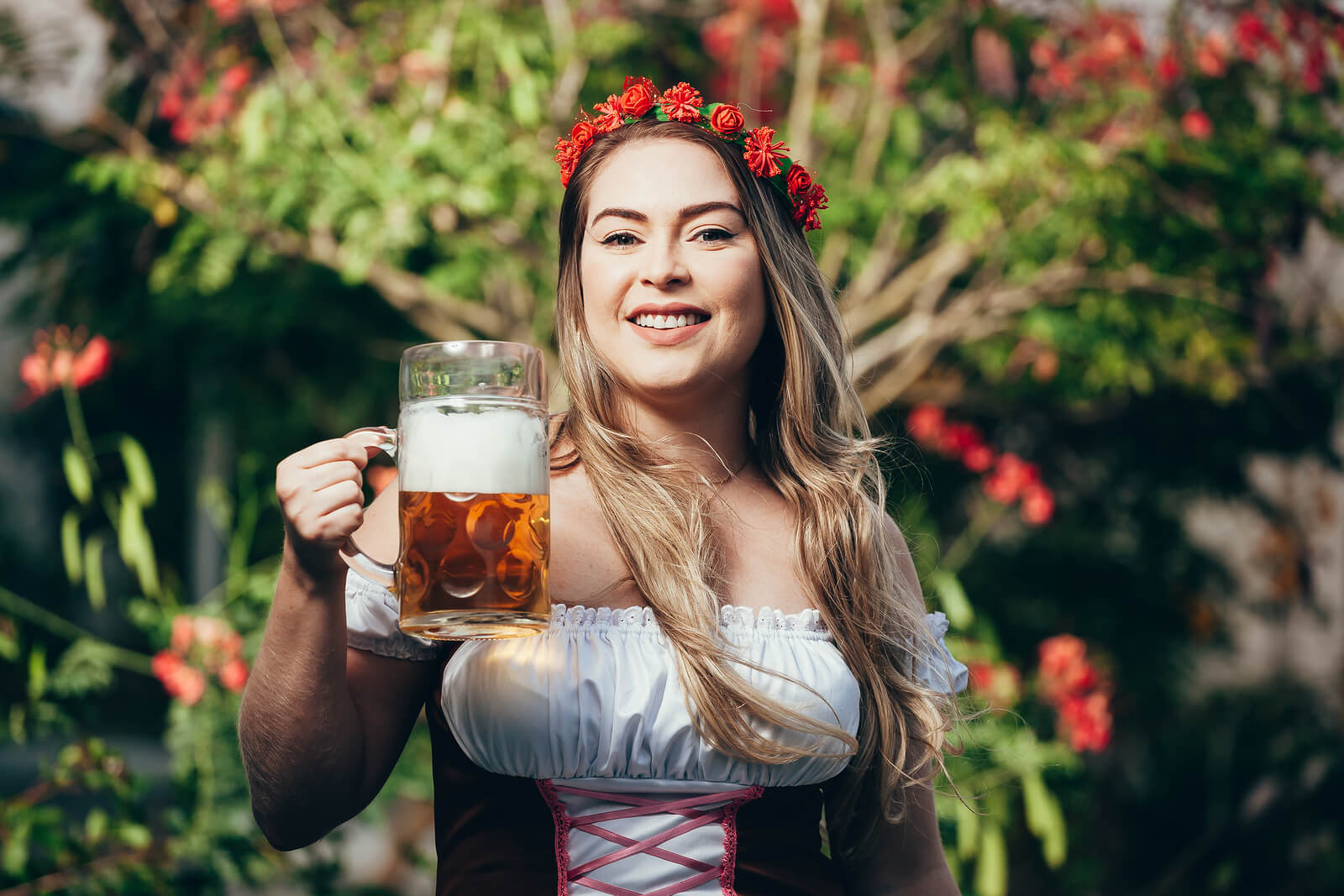 Attractive girl in traditional german costume with pretzel and beer on Oktoberfest